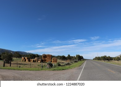 Turnoff to a field in Sanpete county Utah with a barbed wire fence, sagebrush, cedar trees and bales of hay in the distance