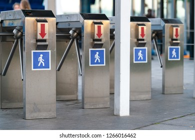 """Turnstiles in subway. Access control system at entrance. Three working turnstiles and one broken. Four gray tourniquets with red arrow-pointer and square sign """"man on blue background"""". No entry"""