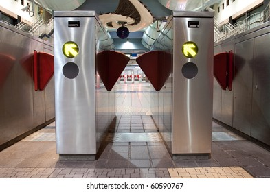 Turnstiles in underground railway station.  Green arrows pointing to the way forwards.  Red barriers preventing progress.