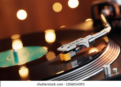 Turntable player with background of a stack of records Christmas tree. Sound technology DJ. Black vinyl record and stylus with needle. Christmas lights bokehPopular Disco Trends 60s, 70s, 80s, 90s