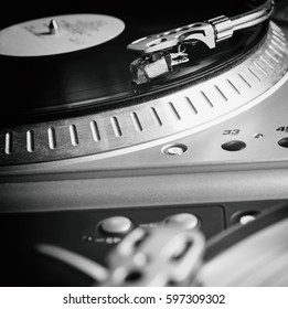 Turntable playing vinyl record with music. Useful equipment for DJ, nightclub and retro hipster theme or audio enthusiast.
