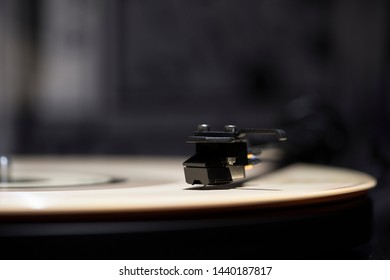 Turntable plays colored vinyl record in abstract background