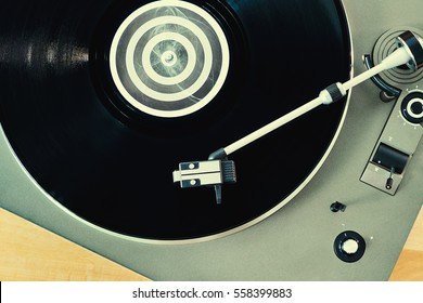 Turntable vinyl record player on a wooden table. Retro audio equipment for disc jockey. Sound technology for DJ to mix & play music. Black vinyl record. Vinyl record and needle close-up