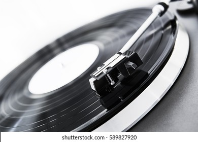 Turntable vinyl record player on a white background. Retro audio equipment for disc jockey. Sound technology for DJ to mix & play music. Black vinyl record. Vinyl record and needle close-up