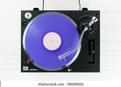 Turntable vinyl record player on the background of their white wooden boards. Sound technology for DJ to mix & play music. Needle on a vinyl record. Purple vinyl record