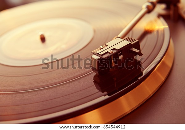 Turntable vinyl record player on the background of a sunset over the lights city. Sound technology for DJ to mix & play music. Black vinyl record. Vintage vinyl record player. Needle on a vinyl record