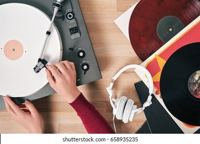 Turntable vinyl record player  with vinyl records and headphones on a wooden table. Hand girl includes gramophone. Sound technology for DJ to mix & play music. White vinyl record