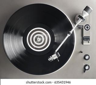 Turntable vinyl record player. Retro audio equipment for disc jockey. Sound technology for DJ to mix & play music. Black vinyl record