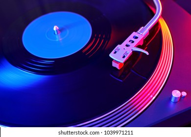 Turntable vinyl record player. Sound technology for DJ to mix & play music. Vintage vinyl record player on a background decorations for a party, bright disco lights. Needle on a vinyl record