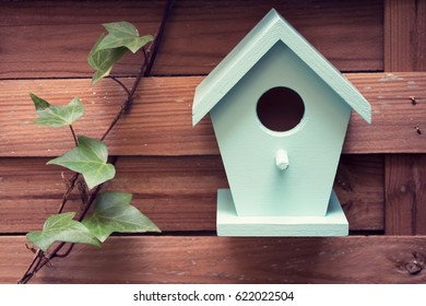 A turquoise bird house hanging from a fence