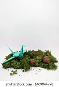 Turquoise bird origami in the grass vertical banner