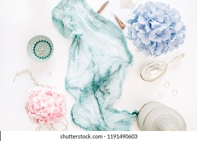 Turquoise blanket, colorful pastel hydrangea flower bouquet, woman fashion accessories on white background. Flat lay, top view.