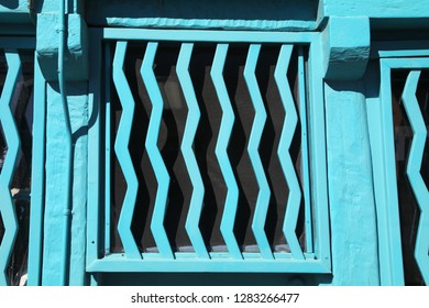 Turquoise blue bars with a wavy shape make an interesting barricade over a window in New Mexico