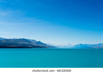 A turquoise blue lake with snow covered mountains in the distance