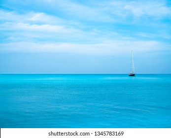 Turquoise blue sea with blue sky and a visible saling boat in distance, floating on horizon.