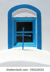 A turquoise and blue window and cross in a white Greek Orthodox Church in a Cyclades island. Suitable to be used like a background.