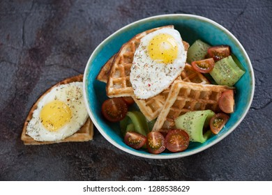 Turquoise bowl with waffles, fried egg and fresh vegetables on a grey stone background, elevated view