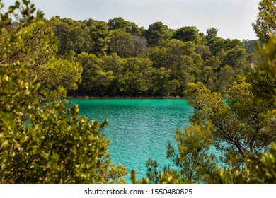 Turquoise bright colored saltwater lakes of the National Park on the island Mljet, Croatia Europe. Mediterranean coast with greenery and trees creating a calm mindful scene.