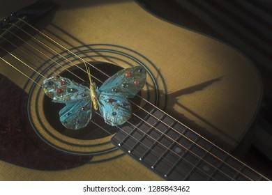 Türkisfarbener Schmetterling auf Streichern akustischer Gitarre, Konzept für Poesie, Musik, Sängerkreativität.