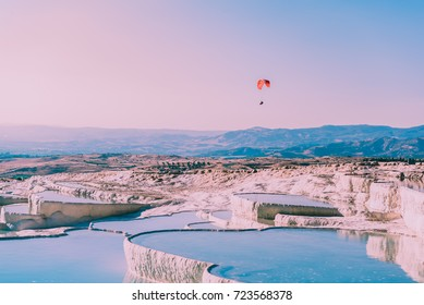 Turquoise color view of Pamukkale (Cotton Castle) is popular with Travertine pools and terraces  and a paraglide on the air.