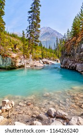 Turquoise colored waters from Tokumm Creek flows through Marble Canyon in Kootenay National Park, British Columbia, Canada, near Banff. Mount Whymper in the background.