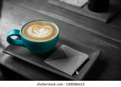 A turquoise cup of coffee with a heart latte foam art on top, sitting on a rectangular saucer and on a wooden table, coffee in color and surrounded in black and white, monochrome.