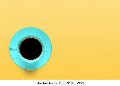 Turquoise cup of coffee on a background of pastel yellow color