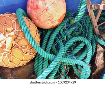 turquoise green thick, ring-folded ropes, next to it floating balls. Close-up in clipping at a fishing port of a fishing village on Tenerife.