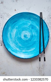 Turquoise hand painted ceramic serving plate with wooden chopsticks on side. Flat lay, top view.