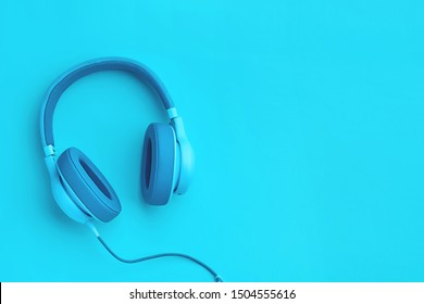 Turquoise headphones a colored background. Music concept with copyspace. Blue headphones isolated