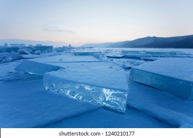 Turquoise ice floe. Winter sunset landscape. Ice-drift of Baikal lake