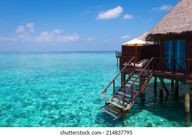 Turquoise lagoon in a tropical ocean, over-water bungalow with steps into the water.