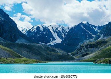 Turquoise lake among mountain peaks. High mountain river on summer day, hiking on rocks and stones
