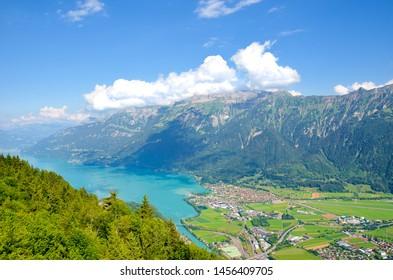 Turquoise Lake Brienz in Interlaken, Switzerland from above from Harder Kulm. Amazing Swiss landscape. Green hills, Swiss Alps. Summer Alpine landscapes. Nature