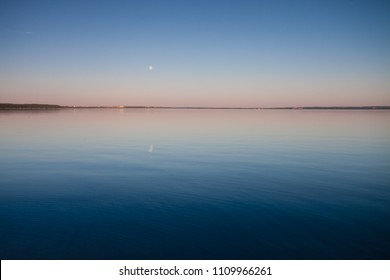 The turquoise lake at dawn. Russia, Yaroslavl region, the city of Pereslavl, Pleshcheyevo lake. smooth blue and turquoise lake surface at dawn, red and orange and sky blue.