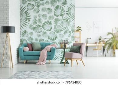 Salão turquesa com cobertor rosa e travesseiros em pé no interior do apartamento elegante com papel de parede floral