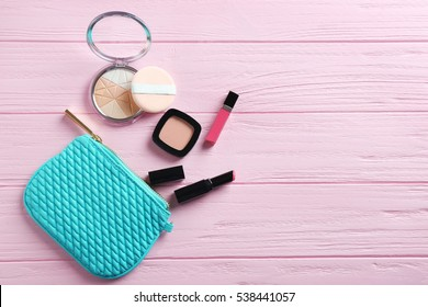 Turquoise make up bag and decorative cosmetics on pink wooden background