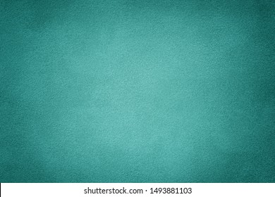 turquoise matte background of suede fabric, closeup. Velvet texture of seamless cyan leather. Felt material with vignette.