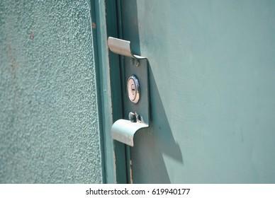 Turquoise Metal Door Lock with Concrete Wall