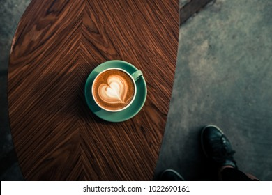 Turquoise mug of flat white coffee with heart shaped latte art on wooden table at the hipster coffee shop.  Vintage color filter effect. Flat lay, copyspace