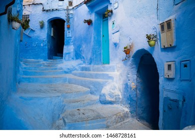 Turquoise narrow street with blue houses and stairway in Chefchaouen in Morocco