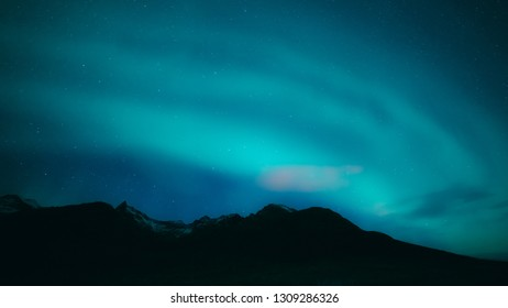 Turquoise northern lights above black mountain silhouettes, Tromso, Northern Norway. Bright stars on indigo blue sky, snow on mountain tops.