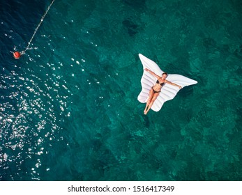 Turquoise ocean water and relaxed swimming woman, aerial drone shot. top down