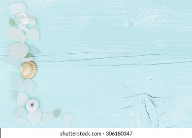 A turquoise painted wooden board with shells and sea glass