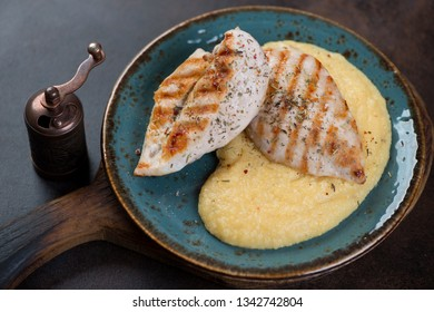 Turquoise plate with fried chicken breast fillet and polenta, horizontal shot on a dark brown metal background