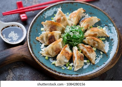 Turquoise plate with pan fried gyoza dumplings, seaweed salad and soy sauce, studio shot, selective focus