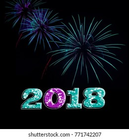 Turquoise and purple fireworks exploding in the night sky with the year 2018 in purple and aqua with white stars Happy New Year New Years Eve concept.