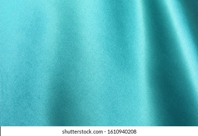 Turquoise satin background. Silk fabric with pleats. Satin, silk or satin create a beautiful drape. Fashion design, background.