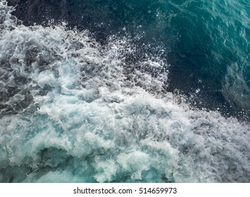 Turquoise sea background, natural color of aqua for your marine design. Texture of sea water with foam and waves, top view.