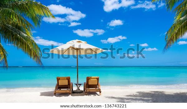 türkisfarbenes Meer, Liegestühle, weißer Sand und Palmen, Sonne, sehr schöne Natur